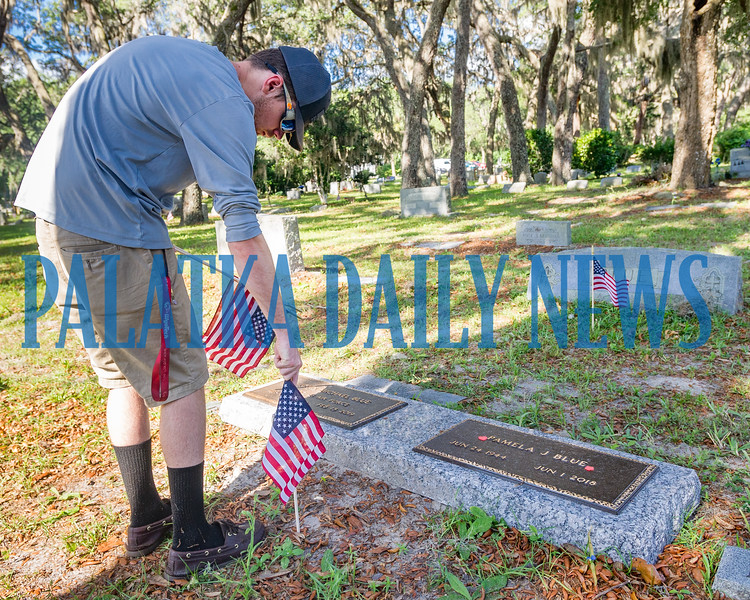 Crescent City High School student David Dowling III, 16, plants a flag on a veteran's grave at the Eden Cemetery in Crescent City on Monday morning. Flags will be placed on veterans' graves in several cemeteries throughout the week to prepare for Memorial Day. Fran Ruchalski/Palatka Daily News