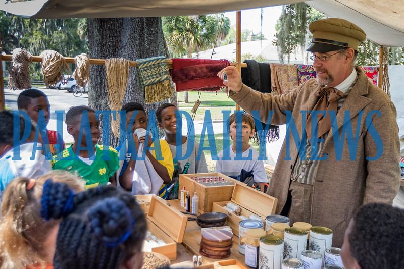 Traveling merchant Gary Graffweg shows students his various wares that he would bring to army encampments to sell to the soldiers during the Civil War at Occupation Palatka on Friday morning. Fran Ruchalski/Palatka Daily News