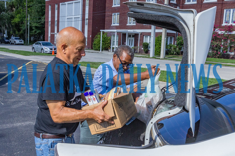 Volunteer Joe Iovino, left, of St. Monica Church helps David Fisher load his food into his car at the Community Food Bank on Thursday morning in the First Baptist Church parking lot. Fran Ruchalski/Palatka Daily News