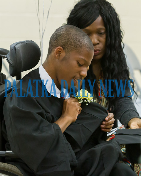 Jarvarious Boynton-DeWitt looks at the flower his mother just pinned on his gown as he graduates from E.H. Miller on Friday morning. Fran Ruchalski/Palatka Daily News