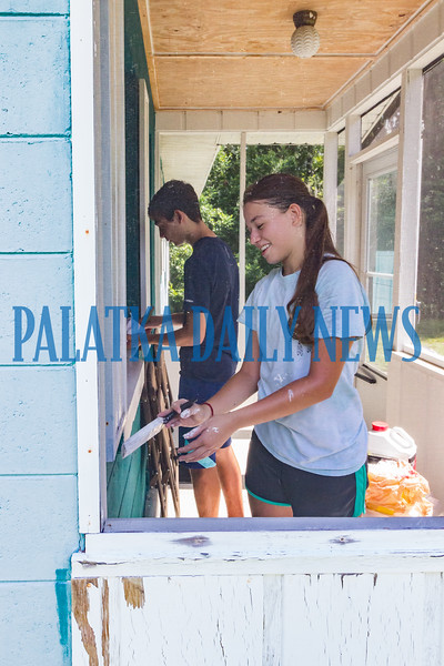 Michael Diana, 16, and Emily Rossello, 16, paint the trim on the porch of a house in the 1100 blk. of N. 12th St. in Palatka. The teens are working in Putnam County as part of the Urban Plunge program run by the Diocese of St. Augustine that allows teens to perform home improvement services for residents in need. Fran Ruchalski/Palatka Daily News