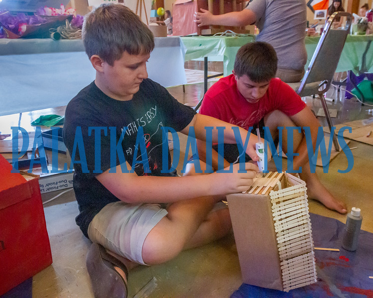 Bryce Edwards, 12, and Isaac Harper, 14, work on building a log cabin to be placed in the Palatka Box City which will be unveiled on Friday afternoon. Fran Ruchalski/Palatka Daily News