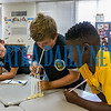 Richard Goodson, 10, center, attempts to put a fourth M&M on a straw while his teammates, Aiden Carter, 11, and Reginald Bryant, Jr., 11, cheer him on during a team-building activity at C. L. Overturf as part of Camp Rise which familiarized the students with the facility and each other on Thursday morning. Fran Ruchalski/Palatka Daily News