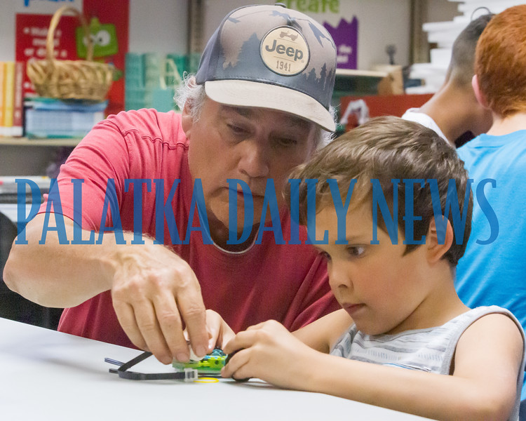 Mark Welbanke and Tegan Bone, 6, work on the robot they're building together at the Lego Robotics Bootcamp at the Palatka Library on Thursday evening. These workshops are open to children and teens ages 6-18 and their parents where they learn the basics of computer programming using simple robots they assemble and program. Fran Ruchalski/Palatka Daily News