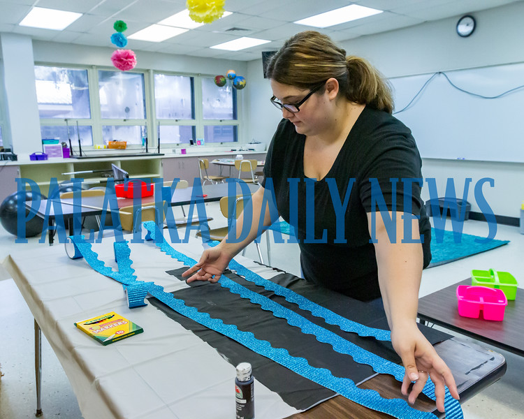 Fourth-grade teacher Erin Fuller works on the decorations she's putting up in her room at Browning-Pearce Elementary School on Tuesday morning. Fran Ruchalski/Palatka Daily News