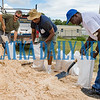 Robert Bley, from left, David Williams, and Roosevelt Lewis fill sandbags at the Putnam County Public Works complex in East Palatka Friday morning while they reminisce about the different hurricanes they've lived through in the past. Fran Ruchalski/Palatka Daily News