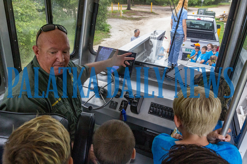 Putnam County Sheriffs Office school resource officer and marine unit deputy Joseph Abbott shows the campers the features of the boat in the cabin. Fran Ruchalski/Palatka Daily News