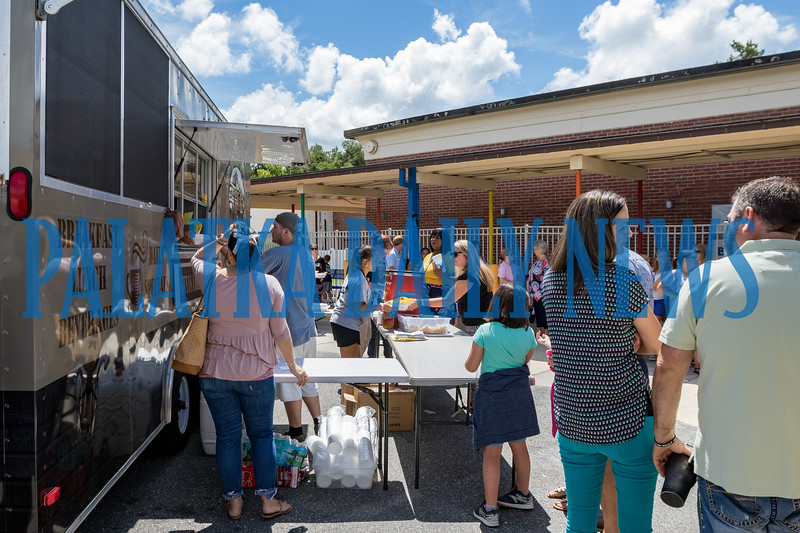Parents, students and staff line up outside Kelley Smith Elementary School for the weekly visit of a food truck to the school on Wednesday at lunch time. The school has scheduled different lunch trucks throughout the year so parents can have lunch with their children on campus. Fran Ruchalski/Palatka Daily News