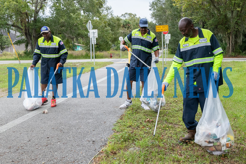 Palatka Public Works employees Eugene Cobbs, from left, Robert Smith and Isiah Seymour pick up debris along the bike trail by 19th Street on Friday afternoon. Fran Ruchalski/Palatka Daily News