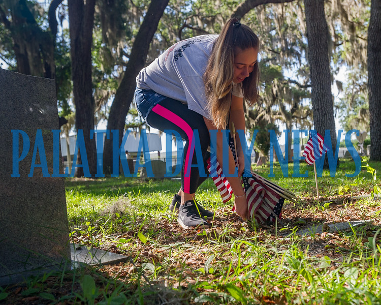 Crescent City High School student Alora Finigan, 16, plants a flag on a veteran's grave at the Eden Cemetery in Crescent City on Monday morning. Flags will be placed on veterans' graves in several cemeteries throughout the week to prepare for Memorial Day. Fran Ruchalski/Palatka Daily News