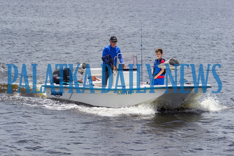 With the help of eleven-year-old Turner Hersey, Sonny Hall brings their boat into the Palatka boat ramp after a family fishing trip on the first day of summer while his wife Marilynn sits with the tuckered out Berkeley Hersey, 4, in the back of the boat.