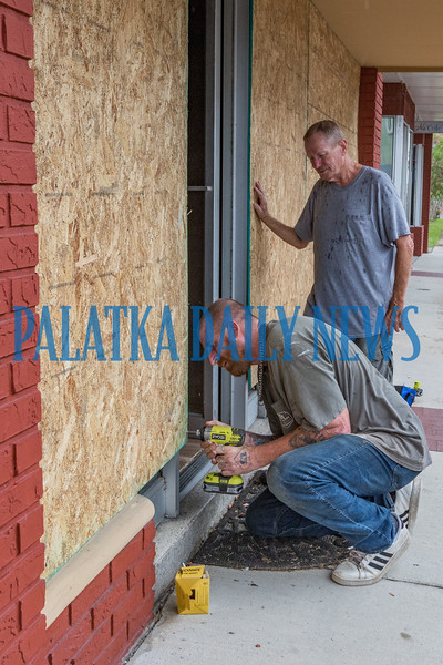 Dru Tribble drills in one of the last screws to hold plywood on the windows at 214 St. Johns Avenue as owner Alvin Price stands by. Both men stated the price of the wood is a small price to pay to protect the store's windows just in case Dorian hits the area. Fran Ruchalski/Palatka Daily News