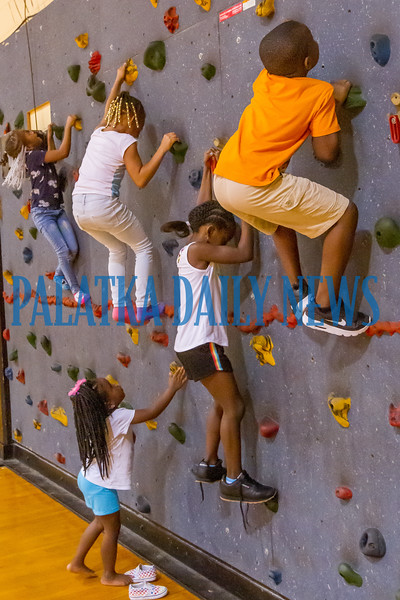 Some of the Kindergarten through second grade kids climb the rock wall in the C. L. Overturf gym on Tuesday afternoon during Camp Higher Ground sponsored by the Police Athletic League. Fran Ruchalski/Palatka Daily News