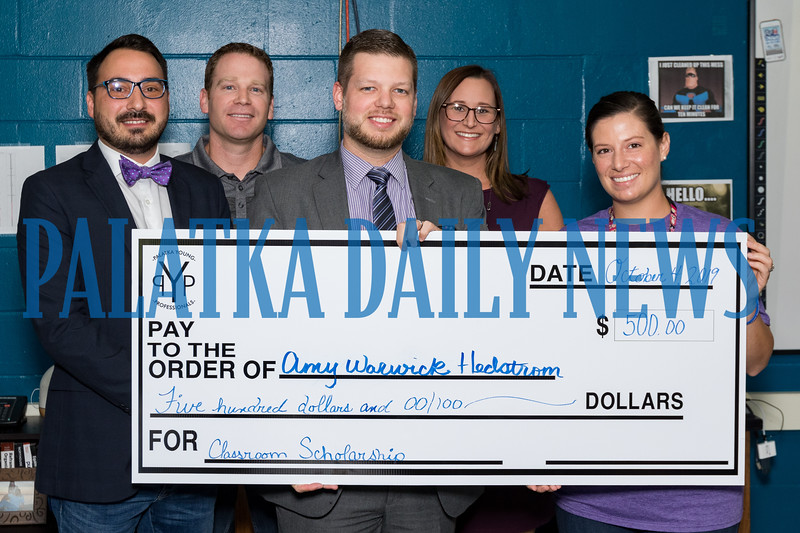 Jenkins Middle School teacher Amy Warwick Hedstrom, right, received a $500 grant from the Palatka Young Professionals to help renovate some facilities on the school farm. Members of the PYP pictured from left are Seth Miles, Benji Bates, David Parsons, and Katie Long. Fran Ruchalski/Palatka Daily News