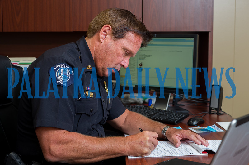 Crescent City Police Chief Mark Carman deals with some of the paperwork that comes with police work. Fran Ruchalski/Palatka Daily News