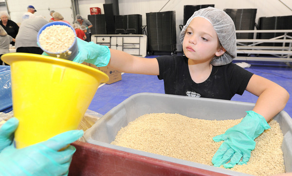 Dacey Ramsey, 7, helps fill a bag with rice during the Victory 4 Haiti event on Saturday at Victory.<br /> Globe | Laurie Sisk