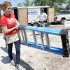 Laura Zemann, one of nine volunteers from Thrivent, a St. Louis-based financial group, unloads a ladder from the Habitat for Humanity tool truck on Saturday at 1814 West Fourth St. Also pictured is Habitat for Humanity construction manager Matt McGee.<br /> Globe | Laurie Sisk