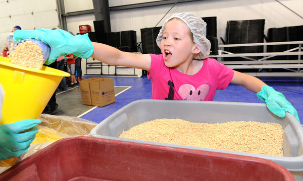 Mia Grubbs, 9, helps fill a bag with rice during the Victory 4 Haiti event on Saturday at Victory.<br /> Globe | Laurie Sisk