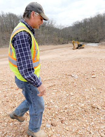 Gary Oplotnik, superintendent for A&M Engineering, walks Thursday  near an area contaminated with lead and zinc that is being capped with clay at Tanyard Hollow. Water from that area will soon flow into Shoal Creek.<br /> Globe | Laurie Sisk
