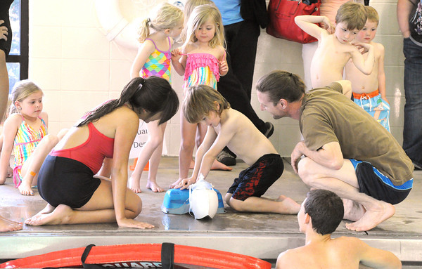 Six-year-old Dennis Bateman III gets a lesson in CPR from YMCA lifeguard Shelby Wilson, left, during the April Pool's Day on Tuesday night at the YMCA's South Branch.<br /> Globe | Laurie Sisk