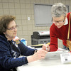 Supervising election judge Quita  Henson, left, helps Andrea Logan sign in to vote on  Tuesday at First United Methodist Church. Logan said both the school board race and the Joplin City Council race prompted her to come out and vote. Henson said there was a significant hike in voter numbers this election at the church, which houses the 12th and 14th precincts.<br /> Globe | Laurie Sisk