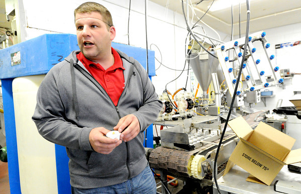 Ott's Foods manager Ryan Brunnert talks about some of the products produced by Ott's in Carthage as he holds one of the portioned dressings.<br /> Globe | Laurie Sisk