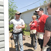 From the left: Habitat for Humanity construction manager Matt McGee teaches volunteers Marita LaChapell, Dan Fuehermeyer and Hilary Wehmeyer how to install vinyl siding on Saturday at 1814 West Fourth St. The volunteers were part of a nine-person group from Thrivent, a financial service company based out of St. Louis.<br /> Globe | Laurie Sisk