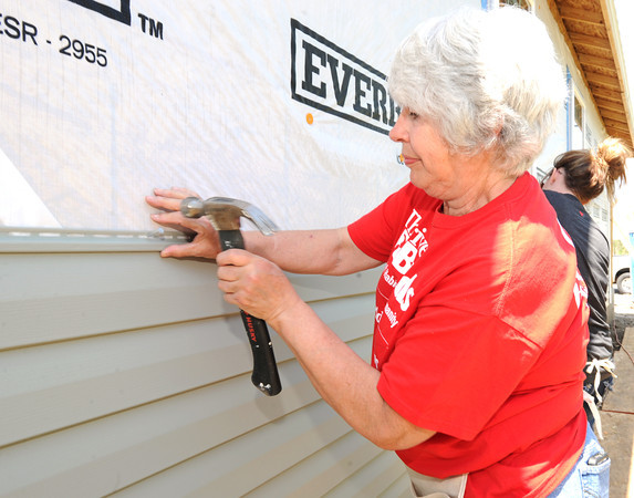 Linda Hill, Laura Zemann, one of nine volunteers from Thrivent, a St. Louis-based financial group, nails siding on a house  at 1814 West Fourth St. on Saturday. <br /> Globe | Laurie Sisk
