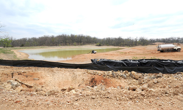 Crews work near a pond built for the landowner at Tanyard Hollow.<br /> Globe | Laurie Sisk