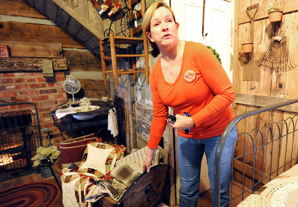Sheila Lynch Calix points out a reproduction of a cradle used by her family in a cabin at the Peel Mansion in Bentonville, Ark. The cabin was moved as a way of perserving it.<br /> Globe   Laurie Sisk