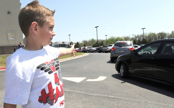Ethan Meeks, 10, helps direct traffic as more volunteers arrive for the Victory 4 Haiti event on Saturday at Victory.<br /> Globe | Laurie Sisk