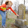 Sheila Lynch Calix rubs the headstone of one of her ancestors buried in a neighborhood cemetery located near the site of a proposed SWEPCO powerline. Some families in the area believe the project will compromise the dignity of the tiny cemetery.<br /> Globe | Laurie Sisk