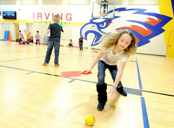 Trinity Crum, 7, plays a game of paddleball during P.E. class on Thursday in Irving Elementary's saferoom.<br /> Globe | Laurie Sisk