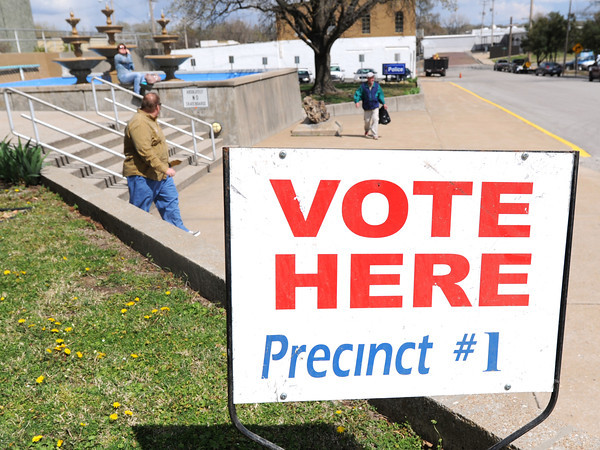 Pedestrians make their way past a sign for 1st Precinct voting at the Donald E. Clark Public Saftey and Justice Center on Tuesday afternoon.<br /> Globe | Laurie Sisk