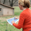 Sheila Lynch Calix looks over a map near the site of a proposed SWEPCO powerline project which overlooks a field of grazing catlle.<br /> Globe | Laurie Sisk