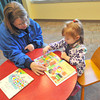 Lynell Saunders, left, shares a book with her three-year-old daughter, Claire Saunders on Saturday at the Carthage Public Library.<br /> Globe | Laurie Sisk