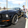 Brett Butler, of webb City, looks over Jane Ballard's 2007 Hertz edition Ford Shelby as Mustang enthusiasts gathered Thursday on Range Line to celebrate the 50th Anniversary of the American muscle car.<br /> Globe | Laurie Sisk