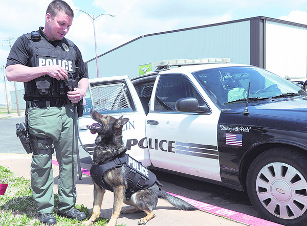 "Joplin Police Department Officer Josh Hanes stands with his K-9, ""Scout"" outside the Joplin Public Safety Training Center on Tuesday. Scout is wearing one of the five new bullet and stab protective vests that were acquired with the help of both an anonymous local couple and Vested Interest in K-9s, a Massachusetts non-profit agency.<br /> Globe 