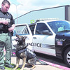 """Joplin Police Department Officer Josh Hanes stands with his K-9, """"Scout"""" outside the Joplin Public Safety Training Center on Tuesday. Scout is wearing one of the five new bullet and stab protective vests that were acquired with the help of both an anonymous local couple and Vested Interest in K-9s, a Massachusetts non-profit agency.<br /> Globe 