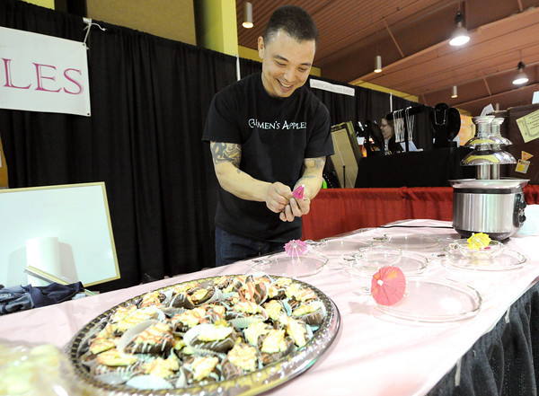 Eric Stuhlman, of Carmen's Apples, readies umbrellas for dipping fruit into a chocolate fountain during the Taste of Home event on Saturday at the Holiday Inn Convention Center.<br /> Globe | Laurie Sisk