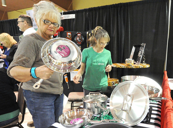 Anna Sossamon, right, of Joe Harding Sales and Service, assists Donna Tinder on Saturday with her selection of cookware at the Taste of Home event at the Holiday Inn Convention Center.<br /> Globe | Laurie Sisk