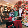 Jack and Becky Walling sit inside a century-old sleigh in the living room of their house at 612 Seville Court. Jack rescued the sled from a barn and placed it in the couple's living room in front of a large Santa and two Christmas trees that form an arc.<br /> Globe | Laurie Sisk