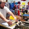 RICHARD LINDSAY — THE BERKSHIRE EAGLE<br /> Owner Brett Simms printing a t-shirt at Twisted Orchard T-Shirt Company in downtown Lee.