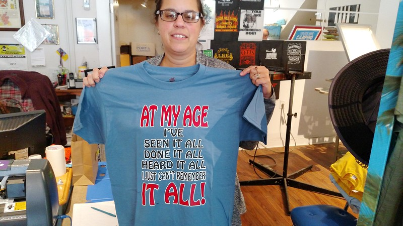RICHARD LINDSAY — THE BERKSHIRE EAGLE<br /> Jennifer Simms of Twisted Orchard T-Shirt Company displays one of the witty t-shirts sold at the Main Street store in Lee.