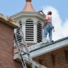 BEN GARVER — THE BERKSHIRE EAGLE<br /> Dave Galipeau of J & D Painting And Restoration paints the cupola on the former Holy Family Church on Seymour Street in Pittsfield.  The building is being transformed into housing units.
