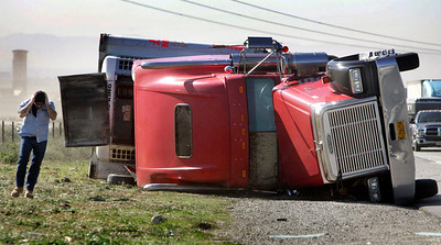 (Fontana)  High winds reeked havoc in the Inland Empire as trucks were toppled over.  This tow truck driver tries to figure out a way to upright this truck on the North  I-15 freeway South of Sierra Ave.