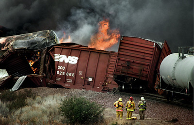 Hazardous material specialists at the site of a derailed train. Toxic black smoke spewed into the air which exploded into flames.  The  train was hauling hazardous chemicals and had jumped the tracks on a steep downgrade. Two people were killed, and 20 others were injured. The 15  freeway was closed in both directions.