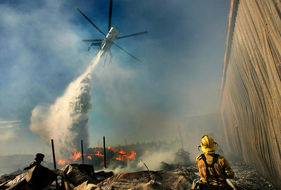 (Fontana) Firefighter, Chris Keith gets help from a water-dropping helicopter that makes a drop at the Industrial yard  where stacks of wooden pallets were stored. The wind-fueled wildfire burned hundreds of acres and  threatened over 100 homes in the area.