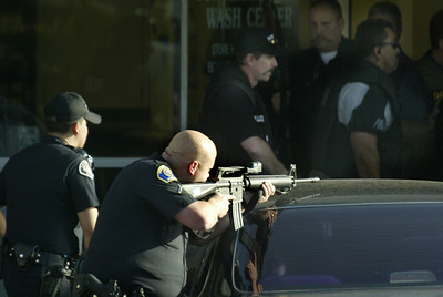 (La Habra)  With their weapons drawn, Police officers swarm a strip mall where one of the suspects shot 2 officers.  The suspect was shot in the back of the mall at 544 West la Habra Blvd.