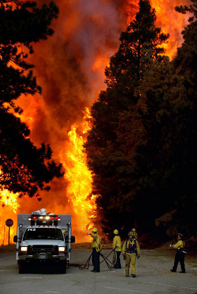 """Burn""  ------   Firefighters are surrounded by a wall of flames as they consume the trees in Sky Forest, South of Lake Arrowhead.  The area was considered the hotspot of the fires that occurred in the Crestline area."